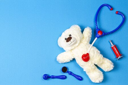 Kids doctor concept. Teddy bear, stethoscope, medical toy kit and medications on blue background. Top view Reklamní fotografie
