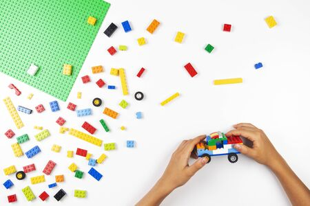 Vilnius, Lithuania - 17 August, 2019: Child hands play with colorful Lego blocks and making new car on white table Redakční
