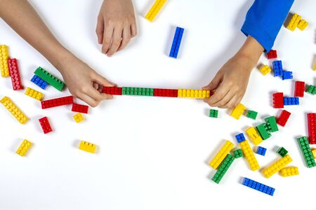 Kids hands playing with colorful building plastic bricks on white background. Educational developing toys background