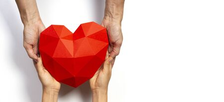 Two persons hands holding red polygonal paper heart shape over white background.
