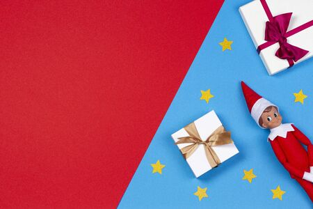 Christmas background. Xmas present gift boxes, decoration stars and toy Santa elf on red and blue background.