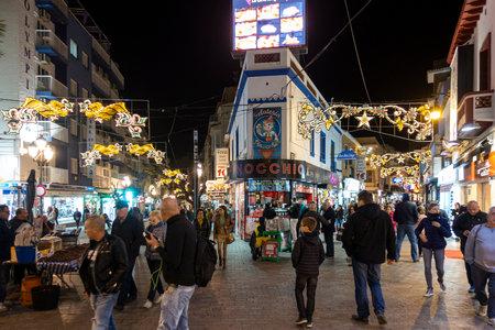 Benidorm, Spain - December 22, 2019: Christmas in Benidorm. People walking on the shopping street in evening time in Benidorm, Alicante, Spain