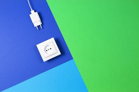 White electrical power socket and power plug on light blue, navy and green background. Top view