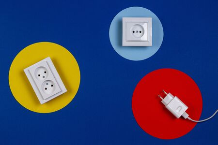 White cable and electrical sockets on geometric yellow red blue navy color background