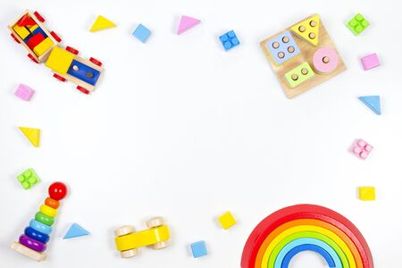 Baby kids toys background. Wooden educational geometric stacking blocks toy, wooden train, rainbow, plane and colorful blocks on white background. Top view