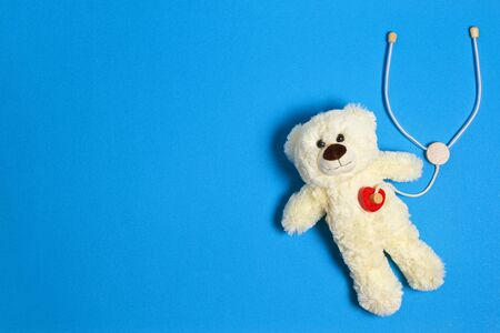 White teddy bear with toy stethoscope on a light blue background. Top view. Copy space for text Stockfoto
