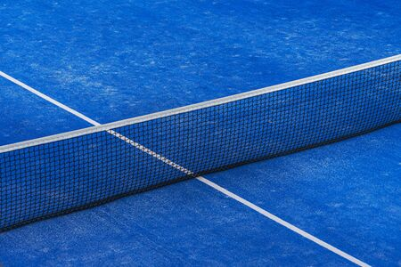 Blue paddle tennis net and court field background.