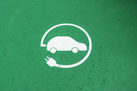 Electric vehicle charging station sign on green road surface background. Top view