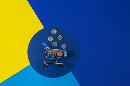 Mini shopping trolley cart with Euro coins on yellow navy blue background. Online shopping, buy, sale, savings, discount concept Stockfoto