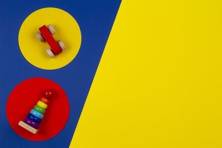 Baby kids toys background. Wooden stacking pyramid tower and red toy car on round yellow and red frames above navy blue background