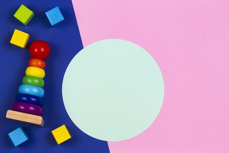 Baby kids toys wooden stacking pyramid tower and wood bricks on pink and blue navy background with blank round light green frame for text or image