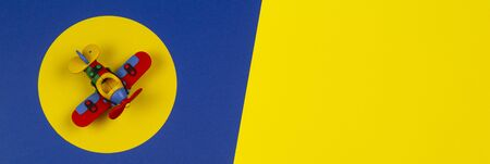 Baby kids toys banner background. Toy red airplane on round yellow frame above navy blue and yellow background