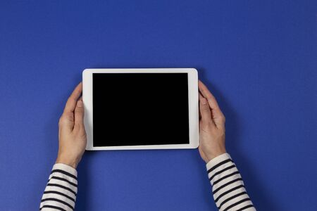 Female hands holding digital tablet computer on navy blue background. Top view