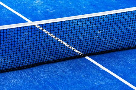 Blue paddle tennis court field with net background.
