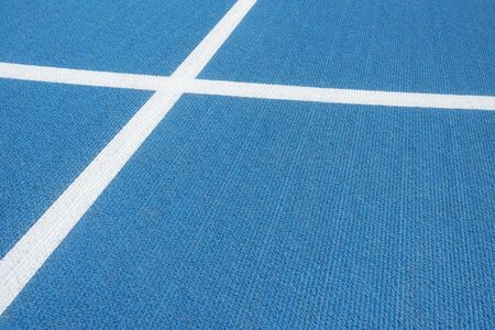 Sport background. Blue running track with white lines in sport stadium