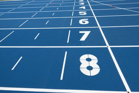 Blue running treadmill track with lane numbers in stadium outdoors.