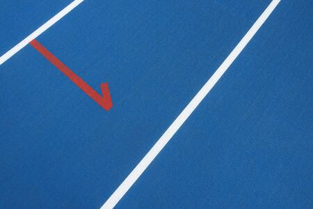 Blue running track with white lines and red mark in sport stadium. Top view