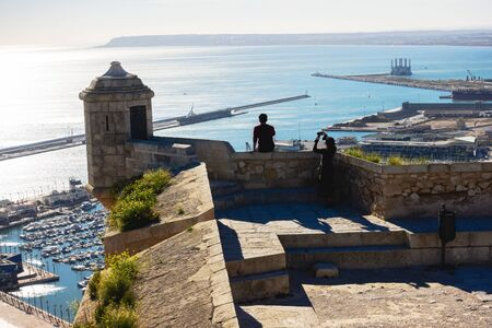 Alicante, Spain - December 23, 2019: Tourist looking at cityscape and making mobile photos on the top of castle tower, Santa Barbara, Alicante Spain Redakční