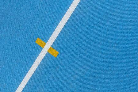 Sport background. Blue running track with white lines and yellow mark in sport stadium. Top view Stockfoto