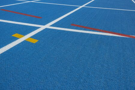 Sport background. Blue running track with white lines, yellow and red mark in sport stadium. Top view