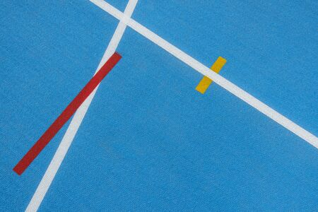 Blue running track with white lines, yellow and red mark in sport stadium. Top view