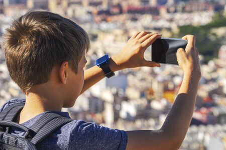 Boy with smartphone in his hands takes photo of Alicante city from Santa Barbara castle in Alicante, Spain