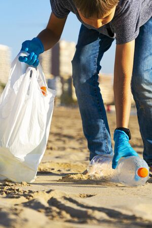 Cleaning city beach from plastic trash. Kid picking up plastic bottle trash from the beach and putting into plastic bag for recycle