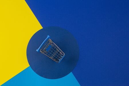 Mini shopping trolley cart on yellow navy blue background. Online shopping, buy, sale, discount concept