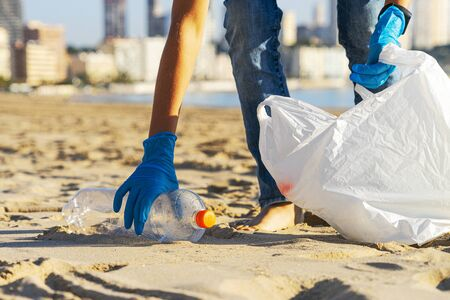 Clean beach from plastic. Hand picking up plastic bottle trash from the beach and putting into plastic bag for recycle. Stockfoto