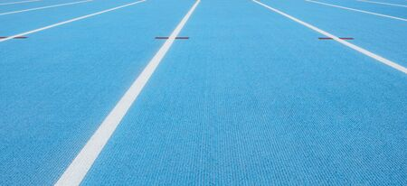 Blue running track with white lines and red mark in sport stadium Stockfoto