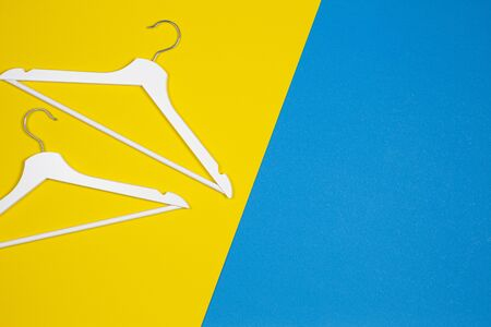 White wooden clothes hangers on yellow and light blue background. Shopping, sale, promo, new season concept Stockfoto