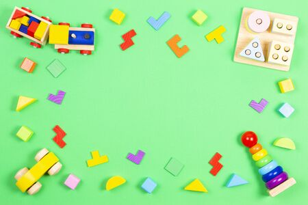 Baby kids toys background. Wooden educational geometric stacking blocks toy, wooden train, car, colorful blocks and wood puzzles on green background Stockfoto