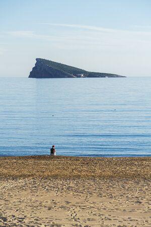 Unrecognizable woman in Santa hat sitting alone in empty beach with Mediterranean sea and Benidorm island background Stockfoto