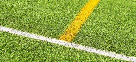 Green artificial grass turf soccer football field backgrond with white and yellow line boundary. Top view