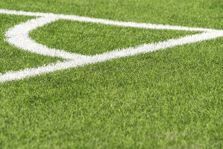 Green artificial grass turf soccer football field backgrond with white corner line boundary. Top view