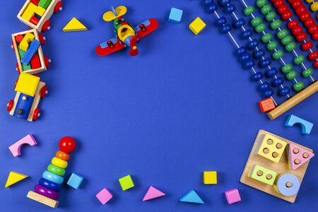Baby kids toys background. Wooden educational geometric stacking blocks toy, wooden train, red airplane and colorful blocks on navy blue background. Top view