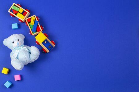Baby kids toys background. Wooden train, blue teddy bear and colorful blocks on navy blue background Reklamní fotografie