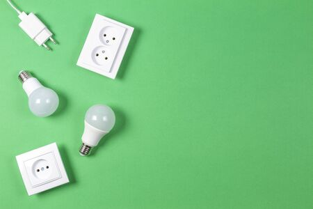 White electrical power sockets, power plugs, light lamp bulbs on light green background. Top view