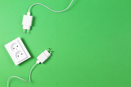 White electrical power sockets and power plug on light green background. Top view