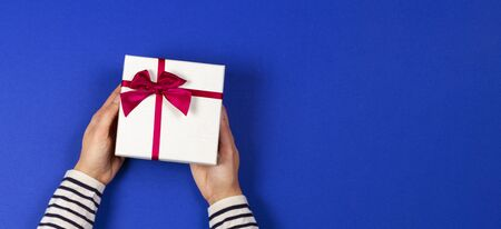 Woman hands holding present gift box tied with ribbon on navy blue background. Top view, place for text. Holiday concept