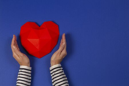 Female hands holding red polygonal heart on blue background. Top view