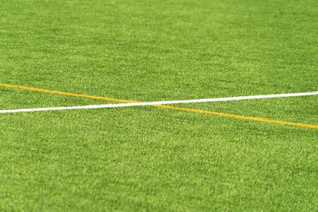 Green artificial grass turf soccer football field background with white and yellow line boundary Stockfoto
