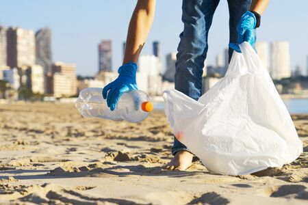 Clean beach from plastic. Hand picking up plastic bottle trash from the beach and putting into plastic bag for recycle. Stock Photo