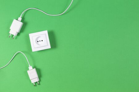 White electrical power socket and power plugs on light green background. Top view