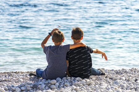 Two boys sitting on the beach and throwing rocks into the sea. Stockfoto