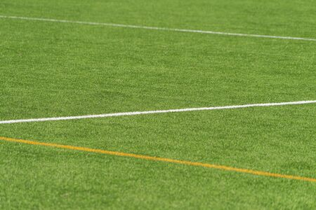 Green artificial grass turf soccer football field background with white and yellow line boundary 写真素材