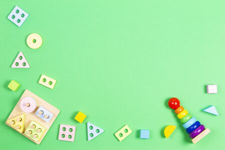 Early childhood development puzzle baby toys. Wooden pastel color geometry educational toy for children and colorful geometric stacking blocks tower toy on light green background. 写真素材