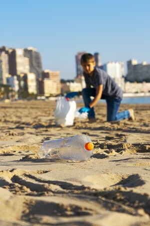 Clean beach from plastic. Hand picking up plastic bottle trash from the beach and putting into plastic bag for recycle. 写真素材