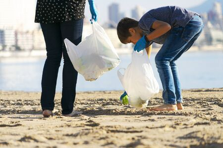 Cleaning city beach from plastic trash. Volunteers picking up plastic bottle. soft drinks cans trash from the beach and putting into plastic bag for recycle 写真素材