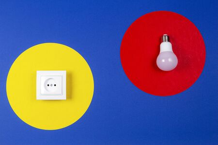 Light lamp bulb and electrical power sockets on geometrical yellow red and navy blue background